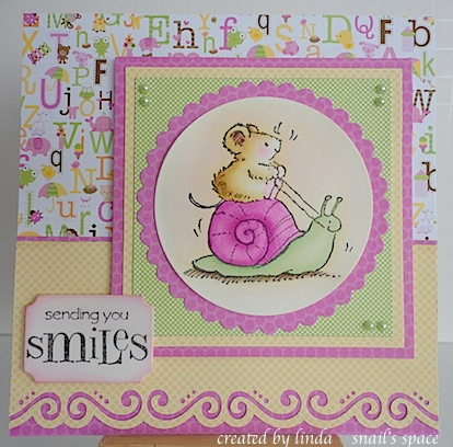 mouse riding a pink and green snail with sending you smiles sentiment and pink, yellow and green papers