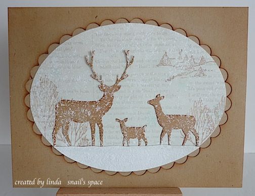 christmas card with deer in snow around trees with a scallop frame surrounding the image
