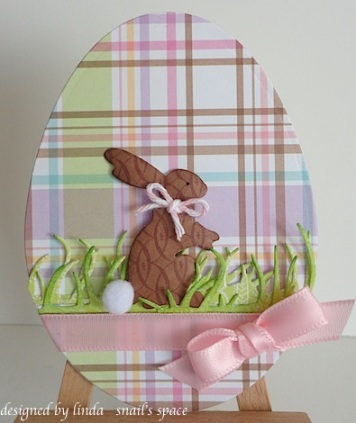chocolate easter bunny with pink bow on an egg shaped card in spring pastel colours
