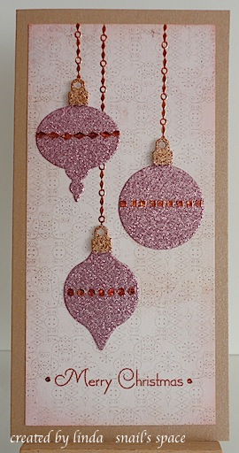 christmas card in pink with three glittery ornaments and merry christmas sentiment