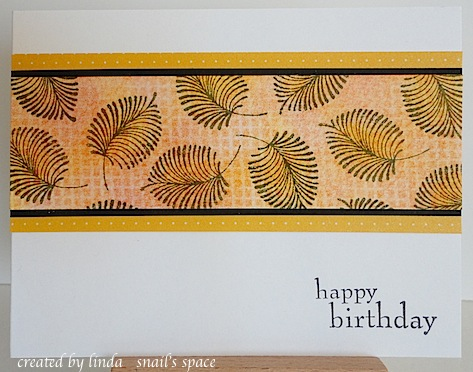 masculine birthday card with orange and yellow strip of paper featuring stamped leaves on a white card base