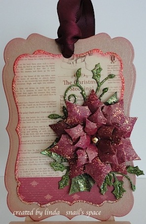 tag with poinsettia and leaves in burgundy, green, beige and glitter with a burgundy bow
