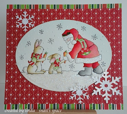 christmas card with santa handing carrots to two brown bunnies wearing scarves coloured in green and red