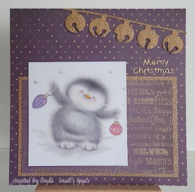 christmas card in purple and gold with a penguin and jingle bells