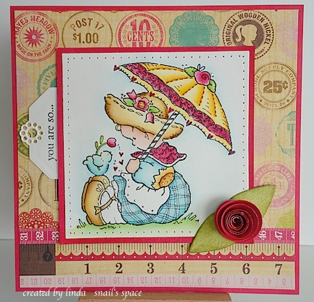 card with girl sitting on ground holding an umbrella with a bird standing on her shoe holding a pink tulip for her with hearts gently falling next to it