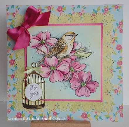 card with bird in a blooming dogwood shrub with a birdcage accent and pink ribbon bow