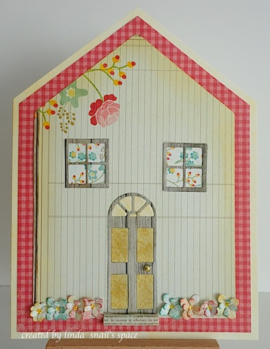 house shaped card in beige, red and turquoise with front door and two windows die cut, a row of flowers at the bottom of the house and a rolled up newspaper at the front door
