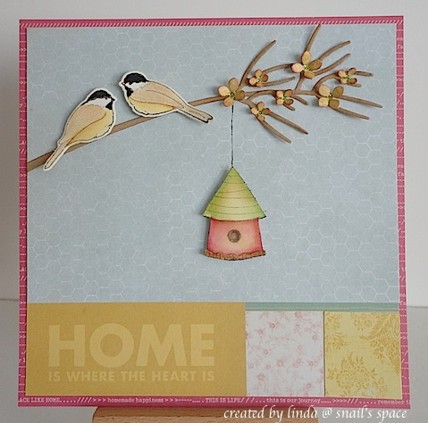 card with two chickadees on a branch, a hanging birdhouse and a home is where the heart is wording