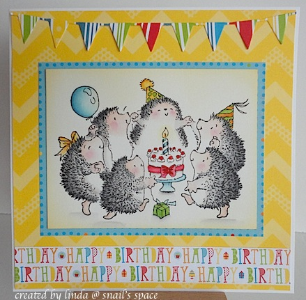 birthday card with yellow background, pennants at the top and featuring a circle of hedgehogs dancing around a birthday cake