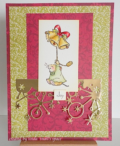 christmas card in red green and gold with mouse flying through the air with gold bells