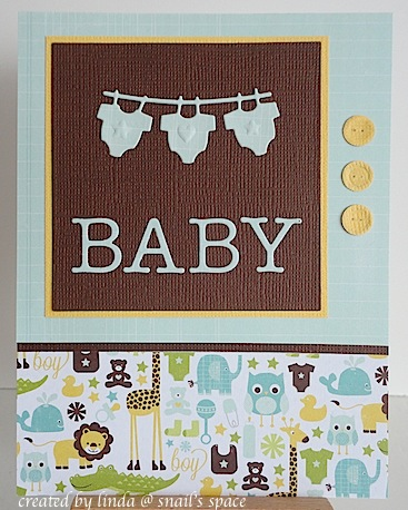 baby card with line of baby clothes, upper case letters spelling baby in browns and blues with animal print on the bottom third and three yellow buttons on the side