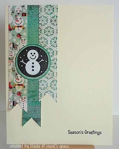 christmas card in teal with snowman and season's greetings sentiment with three printed paper banners