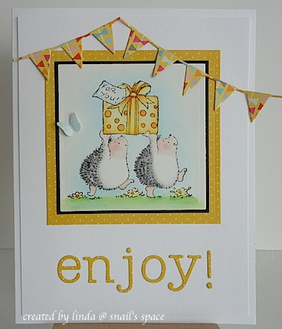 card with two hedgehogs carrying a present, a die cut enjoy sentiment and two die cut pennant borders at the top