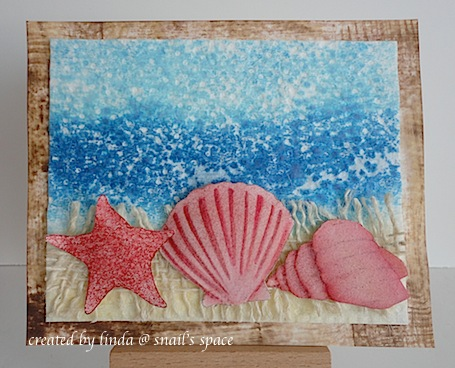 card with beach scene and sea shells in burgundy on a beige mesh ribbon with water and sky in the background