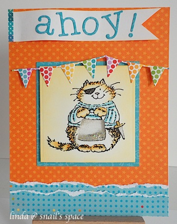 copyright linda @ snailzpace.wordpress.com and described here for people with disabilities; a card with a pirate cat holding a bag of gold on an orange base with blue torn paper strips on the bottom, banners at the top, along with an ahoy sentiment in die cut letters.