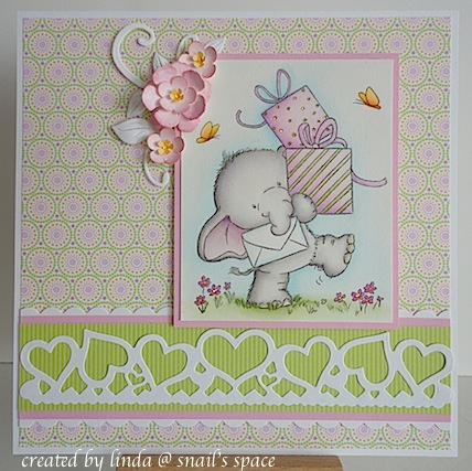 copyright linda @ snail's space and described here for people with disabilities; birthday card in pinks and greens featuring a stamped and coloured cute elephant carrying some presents plus a die cut white heart border at the bottom