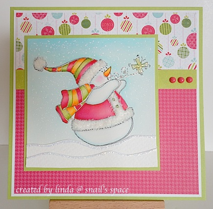 copyright linda @ snail's space and described here solely for people with disabilities; christmas card with bright red, green and blue papers with a snowman wearing a jacket, hat and scarf and a tiny green butterfly nearby