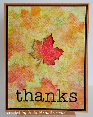 COPYRIGHT LINDA @ SNAIL'S SPACE AND DESCRIBED HERE SOLELY FOR PEOPLE WITH DISABILITIES; a card with fall colours and leaves in the background with one die cute maple leaf in the centre and black die cut letters on the bottom spelling thanks