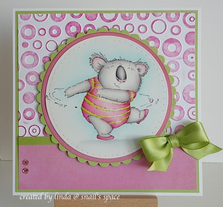 COPYRIGHT LINDA @ SNAIL'S SPACE AND DESCRIBED HERE SOLELY FOR PEOPLE WITH DISABILITIES: a card with a twirling koala in a pink and green leotard with pink slippers, pink dots on white background, a strip of pink paper at the bottom and a green bow
