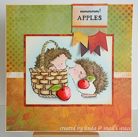 "COPYRIGHT LINDA @ SNAIL'S SPACE and described here solely for people with disabilities; an autumn card with orange, red and green background papers, some banners at the top with a sentiment, ""mmmmm! apples"" and a watercoloured image of two hedgies with apples, one hedgie in a basket"